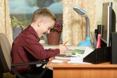 O menino trabalha em seu escritório em um computador pessoal Escreve o te Fotografia de Stock