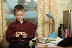 O menino trabalha em seu escritório em um computador pessoal Guarda uma vara Imagem de Stock