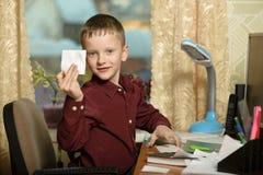O menino trabalha em seu escritório em um computador pessoal Guarda uma vara Foto de Stock