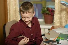 O menino trabalha em seu escritório em um computador pessoal Guarda uma vara Imagens de Stock Royalty Free