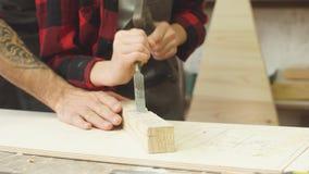 O menino trabalhador trabalha com formão em uma loja da carpintaria video estoque