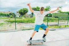 O menino trava o equilíbrio no manual e no deslizamento Foto de Stock