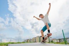 O menino trava o equilíbrio no manual e no deslizamento Imagem de Stock Royalty Free