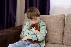 O menino triste abraça seu urso de peluche favorito fotos de stock royalty free