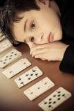 O menino triste coloca sua cabeça na tabela pela fileira dos cartões Imagem de Stock