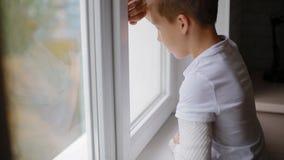 O menino triste com braço quebrado vem à janela vídeos de arquivo