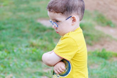 O menino triste considerável pequeno nos vidros olha afastado Imagem de Stock Royalty Free