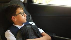 O menino triste está montando no carro na farda da escola 4k, lento-movimento filme