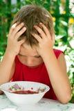 O menino triste pequeno come a sopa Imagem de Stock Royalty Free