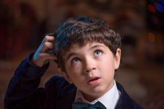 O menino um pouco confundiu e risca sua cabeça na perplexidade imagem de stock royalty free