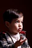 O menino usa os dedos para mostrar como velho é. imagens de stock royalty free