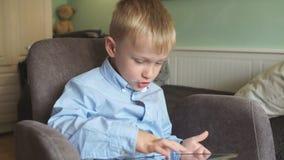 O menino usa a tabuleta em casa vídeos de arquivo
