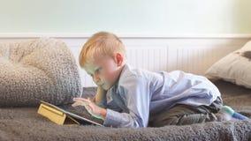 O menino usa a tabuleta em casa video estoque