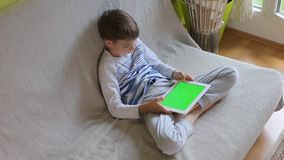 O menino usa a tabuleta, jogos, vista superior vídeos de arquivo