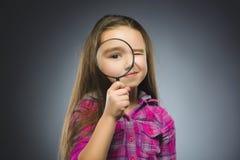 O menino vê completamente a lupa, olho da criança que olha com a lente da lente de aumento sobre o cinza imagem de stock