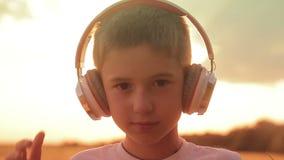 O menino veste fones de ouvido em um campo no por do sol video estoque
