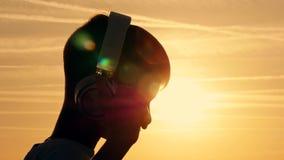 O menino veste fones de ouvido em um campo no por do sol na noite filme