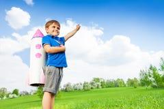O menino veste o brinquedo de papel do foguete e mantém o braço Imagens de Stock Royalty Free