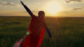 O menino vestiu-se com um cabo do superman que corre em um campo, olhando no por do sol