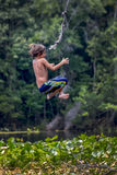 O menino voa para trás - o rio de Wacissa do balanço da corda Fotos de Stock Royalty Free