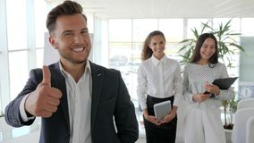 O mentor de sorriso está com os trabalhadores de escritório no centro de negócios, executivo que dá os polegares acima na equipe  vídeos de arquivo