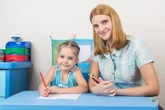 O mentor e a criança idosa de cinco anos tiram com os lápis que sentam-se na tabela Foto de Stock