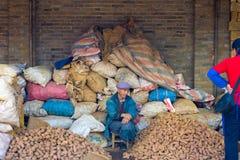 O mercado chinês empilha o vendedor da batata dos sacos Imagens de Stock Royalty Free