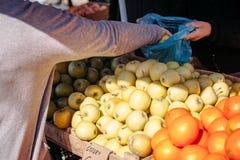 O mercado do comprador compra maçãs fotos de stock royalty free