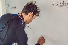O mergulhador escreve um marcador na placa fotografia de stock