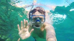 O mergulhador faz o selfie, acenando na câmera - vídeo subaquático filme