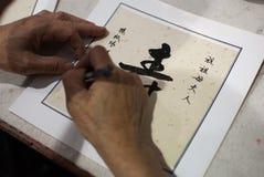 O mestre chinês da caligrafia é escrever Longlife Fotografia de Stock Royalty Free
