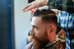 O mestre corta o cabelo e a barba dos homens no barbeiro Fotos de Stock Royalty Free