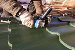 O mestre corta uma folha de metal profissional para a instalação no telhado da casa foto de stock royalty free
