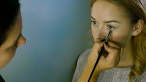 O mestre da composição pinta os olhos da menina Faz a composição, close-up vídeos de arquivo