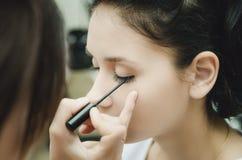 O mestre da composição pinta os olhos da menina Faz a composição, close-up imagem de stock