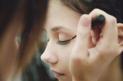 O mestre da composição pinta os olhos da menina Faz a composição, close-up fotos de stock royalty free