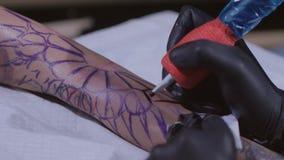O mestre da tatuagem faz a tatuagem no braço Fim da máquina da tatuagem acima Artista que tattooing na oficina Conceito: tattoois vídeos de arquivo