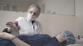 O mestre das testas aplica a pintura na mão do cliente antes de tattooing vídeos de arquivo