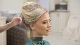 O mestre do cabelo pulveriza o verniz, faz ondas, louro, salão de beleza, movimento lento video estoque