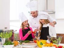 O mestre do cozinheiro chefe e o aluno júnior caçoam meninas em cozinhar a escola fotografia de stock