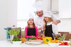 O mestre do cozinheiro chefe e o aluno júnior caçoam meninas em cozinhar a escola fotografia de stock royalty free
