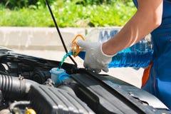 O mestre do serviço do carro derrama o ochetitel de vidro líquido para o inverno, close-up para a manutenção do inverno imagens de stock