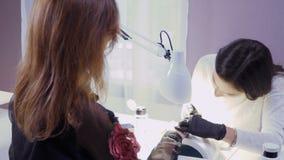 O mestre do tratamento de mãos cobre pregos com a laca uma moça vídeos de arquivo