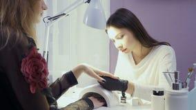 O mestre do tratamento de mãos cobre pregos do ` s da mulher com a laca filme