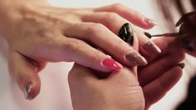 O mestre do tratamento de mãos cobre a unha do ` s da menina no dedo médio de sua mão esquerda com um verniz marrom Close-up video estoque