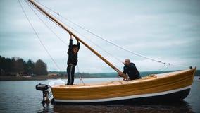 O mestre e seu trabalho assistente no veleiro de madeira no rio tentam instalar o mastro filme