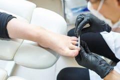 O mestre em luvas pretas no salão de beleza faz o pedicure do tratamento de mãos ao cliente foto de stock royalty free