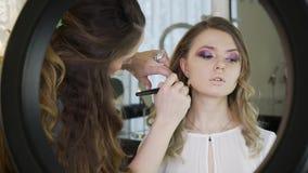 O mestre em uma composição prepara o modelo para a exposição na loja de beleza O maquilhador faz profissionalmente uma composição vídeos de arquivo