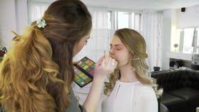 O mestre em uma composição prepara o modelo para a exposição na loja de beleza O maquilhador faz profissionalmente uma composição video estoque