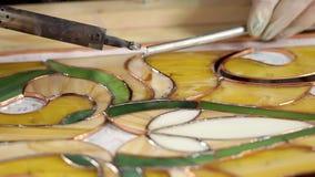 O mestre está criando um painel do vidro colorido usando o ferro de solda para fixar